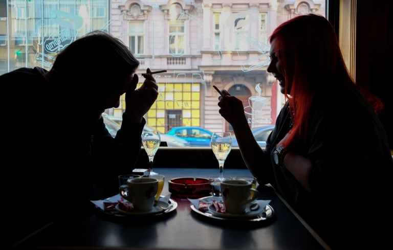 Guests of a Vienna's Cafe/Bar smoke cigarettes with their drinks in Vaienna, Austria, on March 22, 2018. Austrian parliament has announced today that a planned ban on smoking in all bars and restaurants that was due to come into force in May of 2018 will be scrapped. / AFP PHOTO / JOE KLAMAR